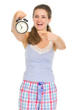 Happy woman in pajamas pointing on alarm clock Royalty Free Stock Images