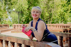 Happy woman in park with a red handbag. Happy woman in the park with a red handbag has leaned on a handrail royalty free stock images