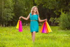 Happy woman at park with shopping bags Stock Photo