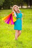 Happy woman at park with shopping bags Stock Photography