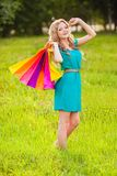 Happy woman at park with shopping bags Royalty Free Stock Photos
