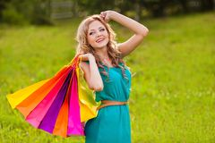 Happy woman at park with shopping bags Royalty Free Stock Images