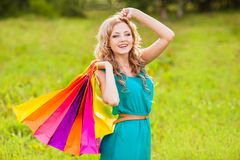 Happy woman at park with shopping bags Royalty Free Stock Photography