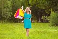 Happy woman at park with shopping bags Stock Image