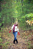 Happy woman on path. A young woman on a path in the woods, fun flirty pose royalty free stock images