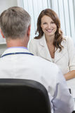 Happy Woman Patient Meeting With Male Doctor in Office Stock Photos