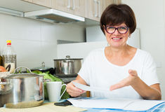 Happy woman paying bills. Cheerful retiree woman sitting on her kitchen and paying bills Stock Photos