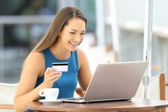 Happy woman paying on line in a restaurant. Single happy woman paying on line with a credit card and a laptop in a restaurant Royalty Free Stock Images