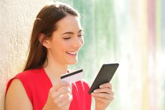Happy woman pays online with credit card and smart phone royalty free stock photo
