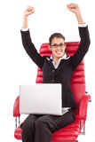 Happy woman with PC on red chair arms raised Stock Photography