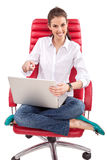 Happy woman with PC on red chair Royalty Free Stock Photo