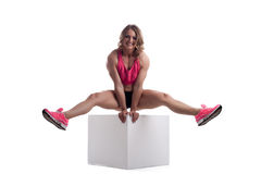 Happy woman with perfect body sit on cube Royalty Free Stock Photos