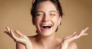 Happy woman with perfect skin. Photo of brunette girl showing empty copy space on beige background. Youth and Beauty Royalty Free Stock Photos
