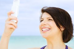 Happy woman with phone on the beach Royalty Free Stock Photos