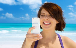 Happy woman with phone on the beach Stock Photos
