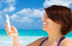 Happy woman with phone on the beach Stock Photography
