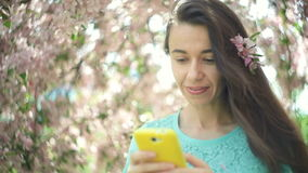 Happy woman with a phone in a blooming spring garden.  stock footage