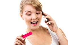 Happy woman with phone informing someone about positive pregnancy test. Happy delighted woman looking at pregnancy and talking on mobile phone, informing someone royalty free stock images