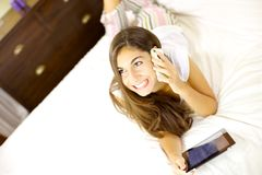 Happy woman on the phone lying in bed with tablet Stock Photos
