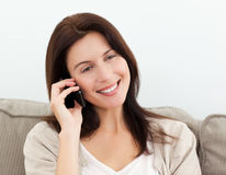 Happy woman on the phone sitting on the sofa Stock Images