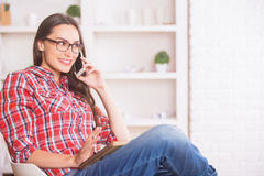 Happy woman on phone taking notes. Portrait of happy smiling woman talking on phone while taking notes in copybook Royalty Free Stock Image
