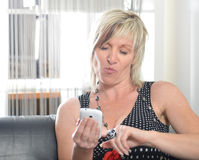 Happy woman phone talking. Face with toothy smile. Blond woman using her white smartphone Royalty Free Stock Images