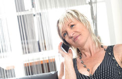Happy woman phone talking. Face with toothy smile. Blond woman using her white smartphone Royalty Free Stock Photo