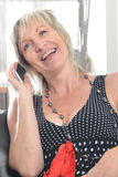Happy woman phone talking. Face with toothy smile. Blond woman using her white smartphone Royalty Free Stock Image