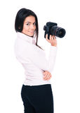 Happy woman photographer holding camera. Isolated on a white background Stock Photos