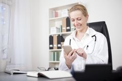 Happy Woman Physician Chatting at her Mobile Phone Stock Photo