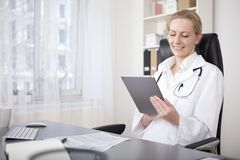 Happy Woman Physician Using her Tablet Device Royalty Free Stock Photos