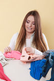 Happy woman picking clothes up in messy room. Royalty Free Stock Photography
