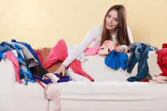Happy woman picking clothes up in messy room. Stock Photos