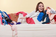 Happy woman picking clothes up in messy room. Stock Images