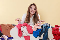 Happy woman picking clothes up in messy room. Royalty Free Stock Image