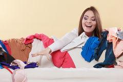 Happy woman picking clothes up in messy room. Royalty Free Stock Images