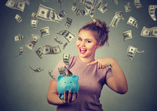 Happy woman with piggy bank celebrates success under money rain falling down dollar bills Stock Images