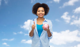Happy woman with piggy bank showing thumbs up Stock Image