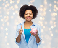 Happy woman with piggy bank showing thumbs up Royalty Free Stock Photos