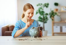 Happy woman with piggy money bank at home. financial planning concept stock image