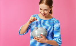 Happy woman with piggy money bank on pink background. financial planning concept royalty free stock photo