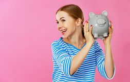 Happy woman with piggy money bank on pink background. financial planning concept royalty free stock image