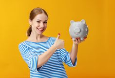 Happy woman with piggy money bank on pink background. financial planning concept stock photography
