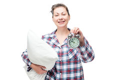 Happy woman with a pillow in her hand shows later time. On the alarm clock Royalty Free Stock Photo