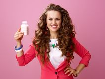 Happy woman on pink background showing farm organic yogurt Stock Photos