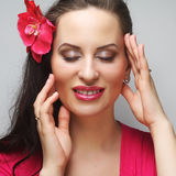 Happy woman with pink flower in the hair. Young happy woman with pink flower in the hair Stock Photo
