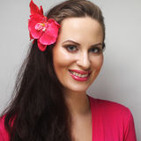 Happy woman with pink flower in the hair. Young happy woman with pink flower in the hair Stock Photography