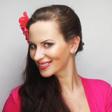 Happy woman with pink flower in the hair. Young happy woman with pink flower in the hair Royalty Free Stock Images