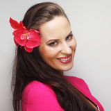 Happy woman with pink flower in the hair. Young happy woman with pink flower in the hair Stock Image