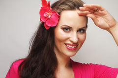 Happy woman with pink flower in the hair. Young happy woman with pink flower in the hair Royalty Free Stock Photos